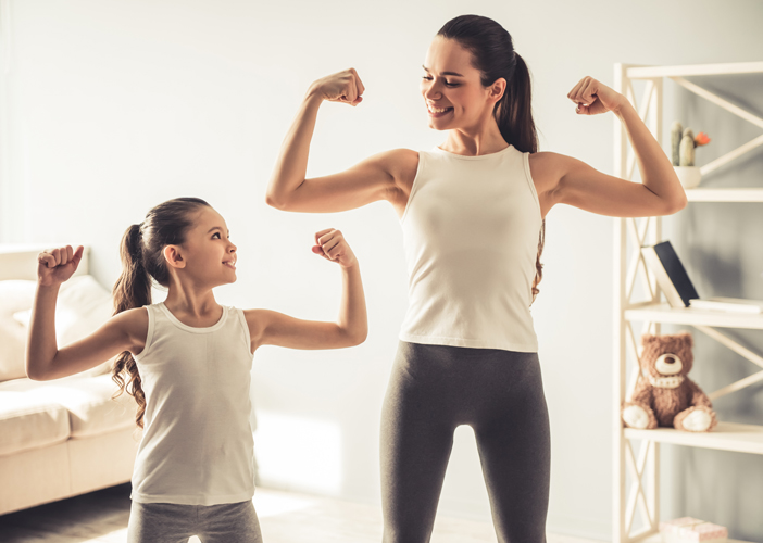 mother and child flexing muscles